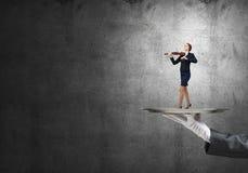Femme d'affaires attirante sur le plateau en métal jouant le violon sur le fond concret Image stock