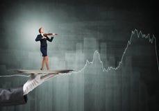 Femme d'affaires attirante sur le plateau en métal jouant le violon et les graphiques au fond Images stock