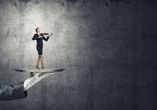 Femme d'affaires attirante sur le plateau en métal jouant le violon sur le fond concret Photographie stock