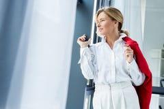 femme d'affaires attirante tenant la veste rouge et regardant loin image libre de droits