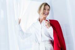 femme d'affaires attirante tenant la veste rouge et regardant loin photos stock