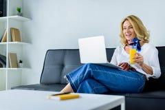 femme d'affaires attirante travaillant avec l'ordinateur portable dans le bureau et tenant le verre photo libre de droits