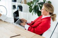 femme d'affaires attirante travaillant avec l'ordinateur portable et les jambes sur la table image stock