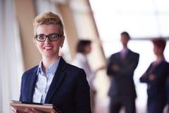 Femme d'affaires au bureau avec le comprimé dans l'avant comme meneur d'équipe Images libres de droits