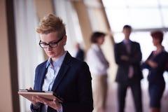 Femme d'affaires au bureau avec le comprimé dans l'avant comme meneur d'équipe Images stock