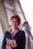 Femme d'affaires au bureau avec le comprimé dans l'avant comme meneur d'équipe Photos libres de droits