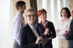 Femme d'affaires au bureau avec le comprimé dans l'avant comme meneur d'équipe Image libre de droits