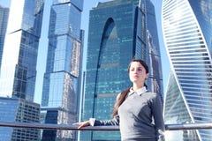 Femme d'affaires au fond de gratte-ciel Photo stock