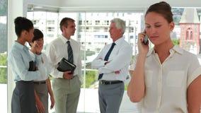 Femme d'affaires au téléphone avec des collègues à l'arrière-plan banque de vidéos