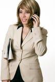 Femme d'affaires au téléphone avec le journal sous le bras photographie stock libre de droits