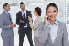 Femme d'affaires au téléphone tandis que parler de collègues Photo stock