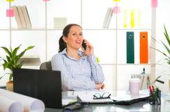 Femme d'affaires au téléphone dans son bureau Images stock