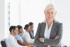 Femme d'affaires avec des bras croisés et des cadres à l'aide des ordinateurs images stock
