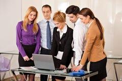 Femme d'affaires avec des collègues regardant l'ordinateur portable Photo libre de droits