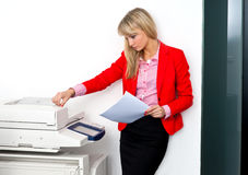 Femme d'affaires avec des documents se tenant à côté de l'imprimante Photographie stock