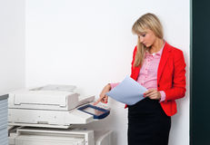 Femme d'affaires avec des documents se tenant à côté de l'imprimante Photo stock
