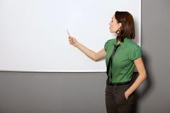 Femme d'affaires avec des mains dans des poches se dirigeant au tableau blanc dans le bureau Photographie stock libre de droits