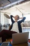 Femme d'affaires avec des mains derrière la tête détendant au bureau image stock