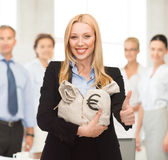 Femme d'affaires avec des sacs d'argent montrant des pouces  Photographie stock libre de droits