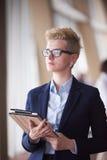Femme d'affaires avec des verres au bureau avec le comprimé dans l'avant As Photo libre de droits