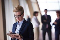 Femme d'affaires avec des verres au bureau avec le comprimé dans l'avant As Photographie stock