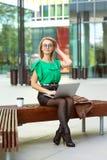 Femme d'affaires avec des verres se reposant sur le banc en dehors du café potable de district des affaires de parc de rue et tra photo stock