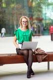 Femme d'affaires avec des verres se reposant sur le banc en dehors du café potable de district des affaires de parc de rue et tra images stock