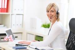 Femme d'affaires avec l'écouteur fonctionnant au bureau Photos stock