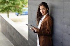 Femme d'affaires avec l'extérieur debout de tablette d'un bureau Photo libre de droits