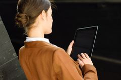 Femme d'affaires avec l'extérieur debout de tablette d'un bureau image stock
