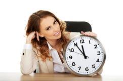 Femme d'affaires avec l'horloge par un bureau Photographie stock libre de droits