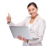 Femme d'affaires avec l'ordinateur portable et le pouce  Photos libres de droits