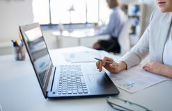 Femme d'affaires avec l'ordinateur portable fonctionnant au bureau photos libres de droits