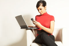 Femme d'affaires avec l'ordinateur portatif et le téléphone Image libre de droits