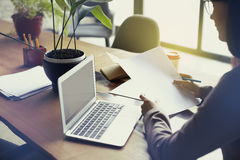 Femme d'affaires avec la feuille de papier de documents dans le bureau moderne de grenier, travaillant sur l'ordinateur portable  Photos libres de droits