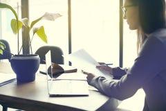 Femme d'affaires avec la feuille de papier de documents dans le bureau moderne de grenier, travaillant sur l'ordinateur portable  Photographie stock