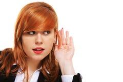 Femme d'affaires avec la main à l'écoute d'oreille d'isolement Image stock