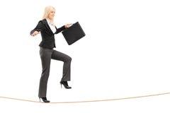 Femme d'affaires avec la serviette, essayant de garder l'équilibre Photographie stock libre de droits