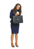 Femme d'affaires avec la serviette regardant sur la montre Photo stock