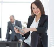 Femme d'affaires avec la tablette à l'arrière-plan du bureau Photos libres de droits