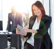 Femme d'affaires avec la tablette à l'arrière-plan du bureau Photographie stock