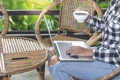 Femme d'affaires avec la tasse de café utilisant l'ordinateur portable dans le matin photos stock