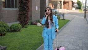 Femme d'affaires avec la valise parlant par le téléphone dans la ville et avoir quelques bonnes nouvelles clips vidéos