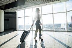 Femme d'affaires avec le bagage dans le vol de attente de terminal d'aéroport international Images stock
