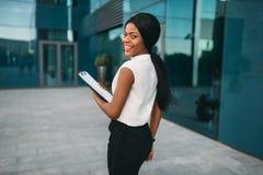 Femme d'affaires avec le bloc-notes dehors, vue arrière images stock