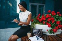 Femme d'affaires avec le bloc-notes se reposant sur le banc images libres de droits