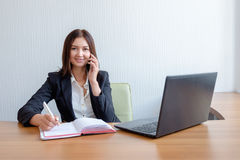 Femme d'affaires avec le carnet, le calendrier et le téléphone portable au travail image stock