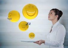Femme d'affaires avec le comprimé regardant des emojis contre le panneau en bois gris illustration de vecteur
