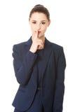 Femme d'affaires avec le doigt sur ses lèvres Photo stock