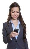 Femme d'affaires avec le long message brun d'écriture de cheveux avec le téléphone Photo stock